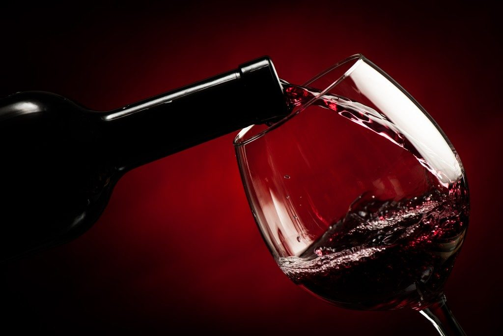 Red wine poured to a wine glass