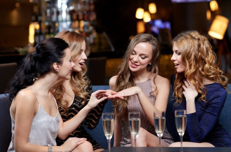 happy woman showing engagement ring to her friends with champagne glasses