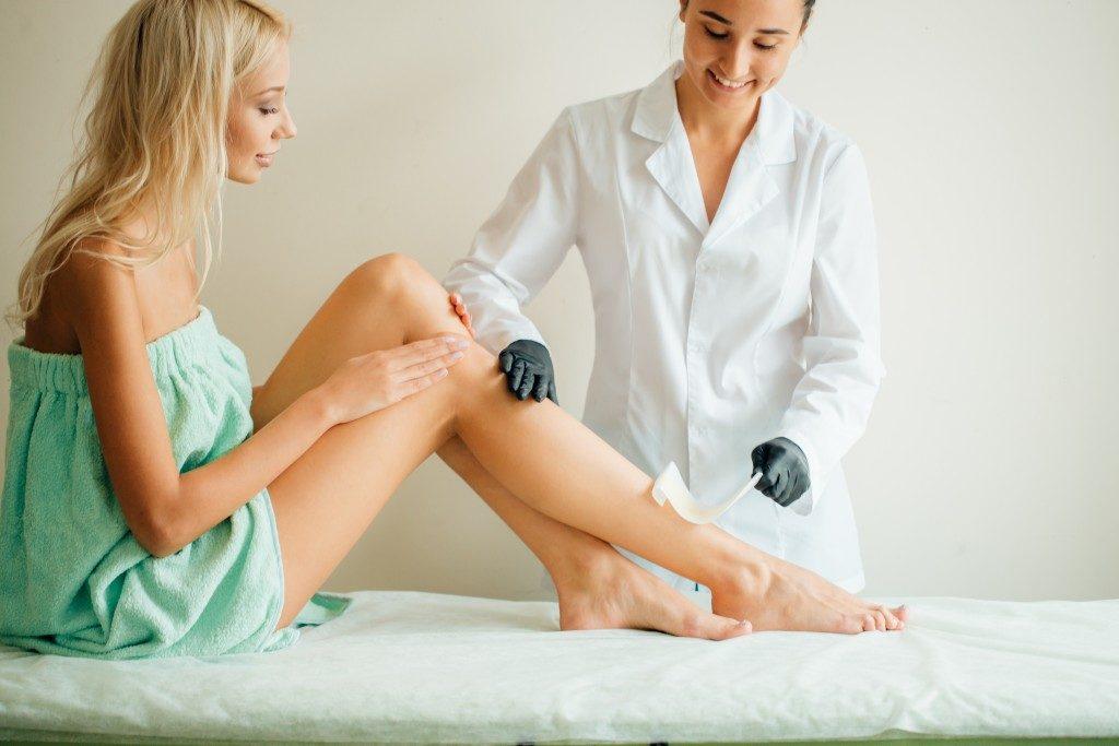 Beautician waxing the woman's leg