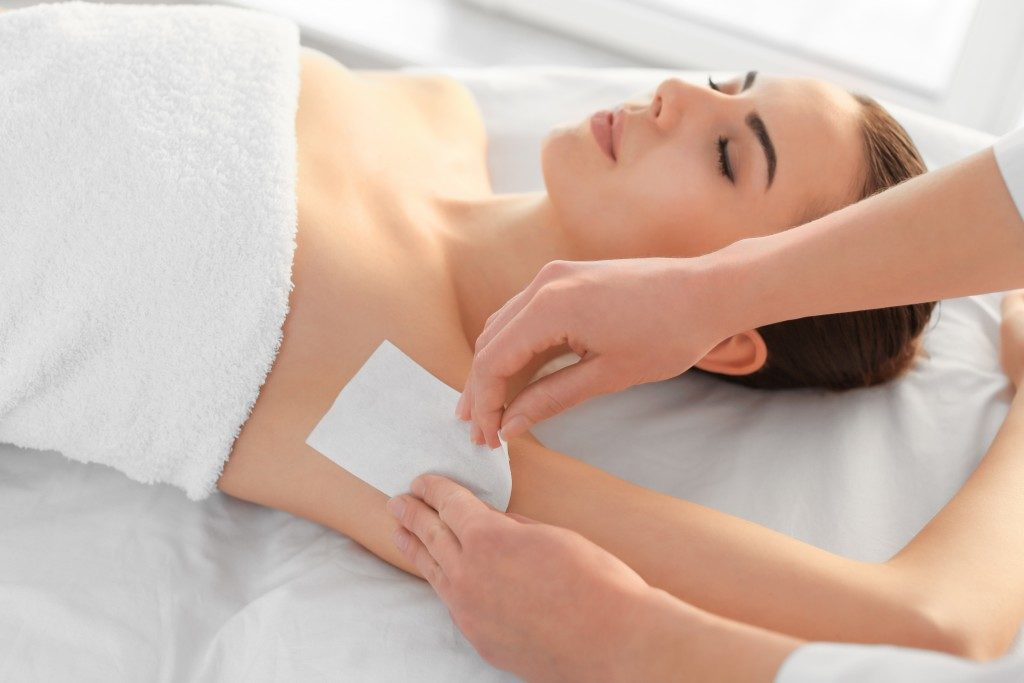 Woman getting her armpits waxed