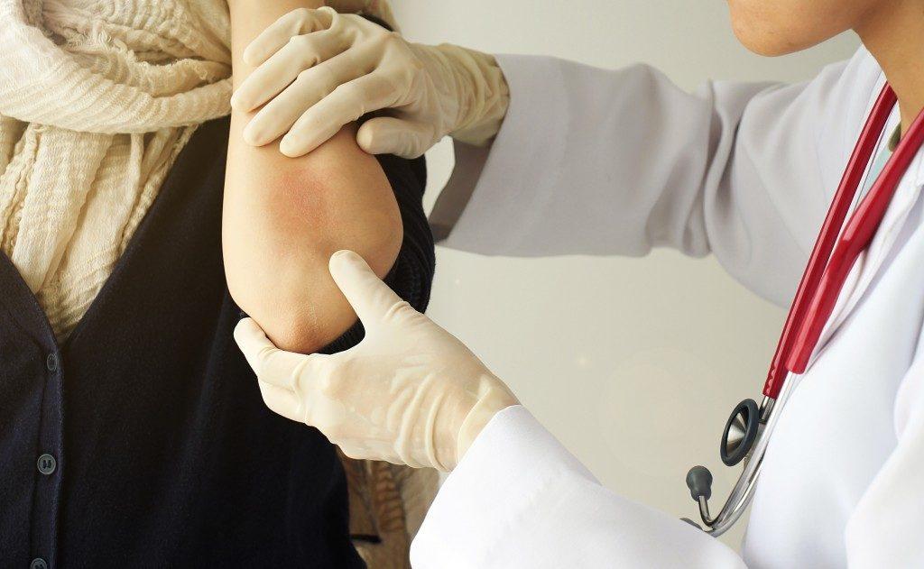 Doctor checking the woman's rash
