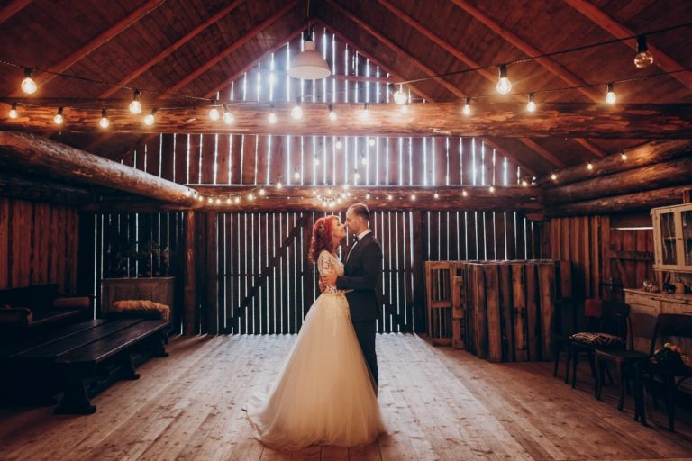 stylish groom and happy bride hugging under retro bulbs lights in wooden barn