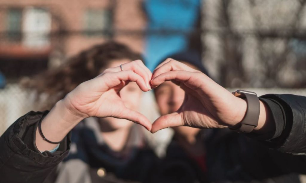 two person combine hand forming a heart hand gesture