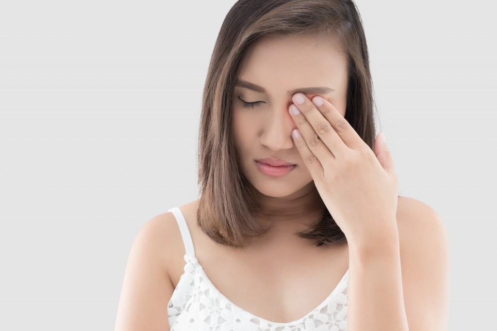 girl rubbing her eye