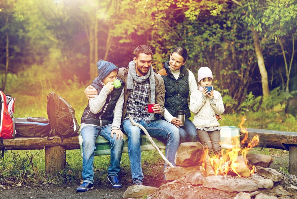 Family camping in the wild and beside campfire