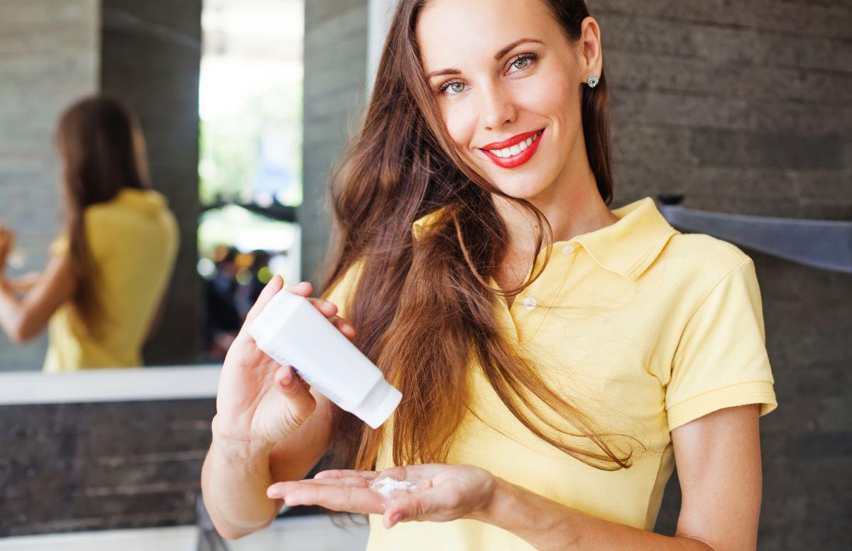 woman applying dry shampoo on her hair.
