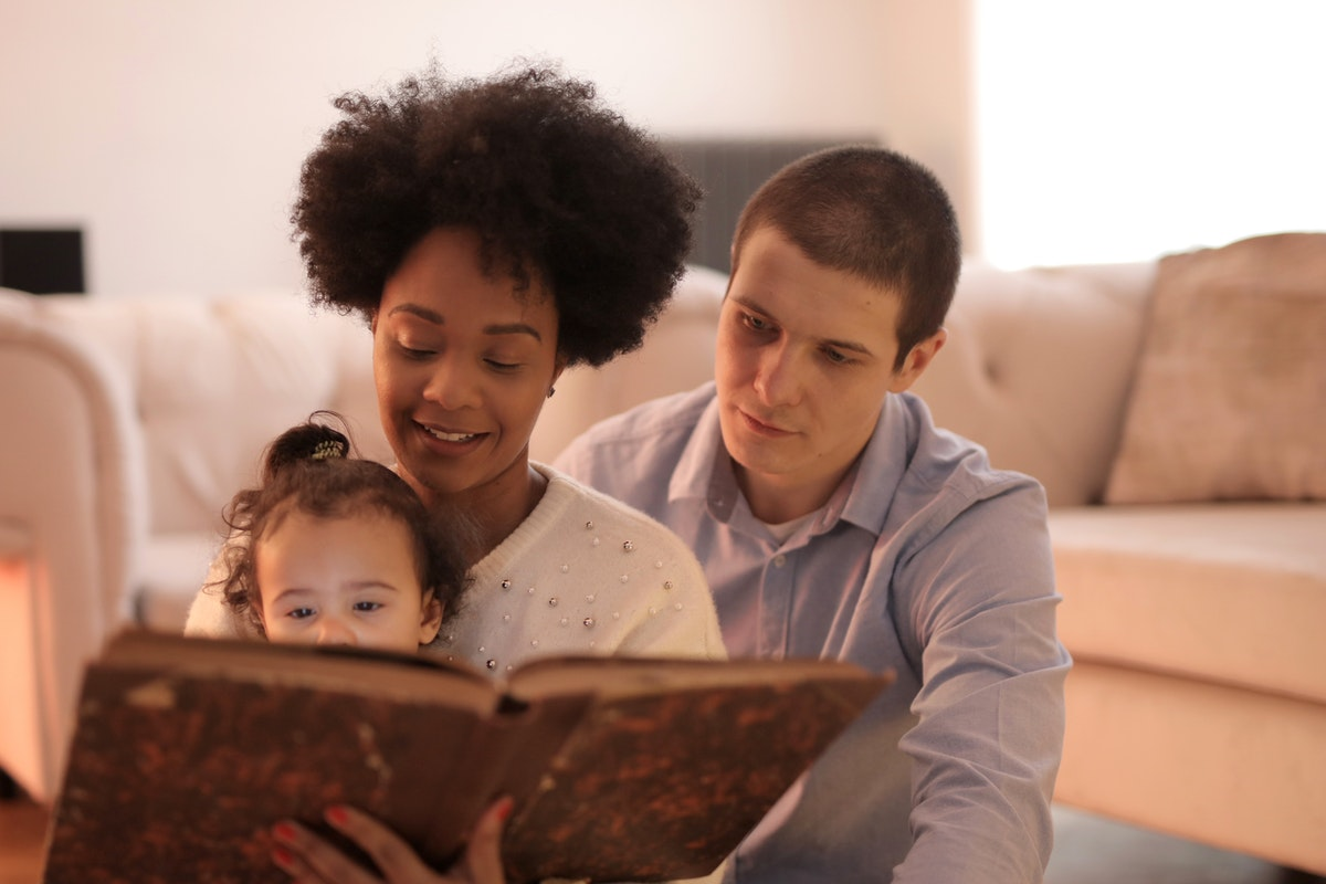 parents reading book to toddler