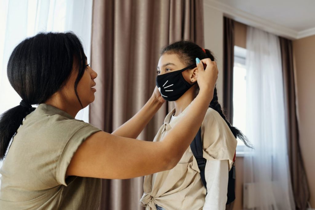 mother putting facemask on her daughter